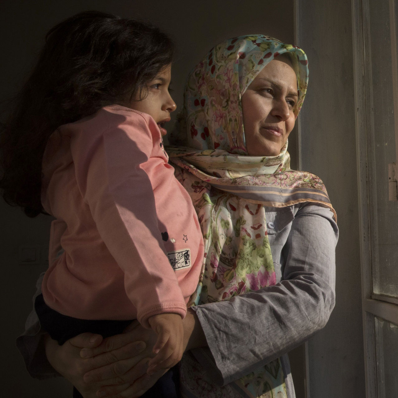 Zahra's mother holds her to look outside at their small garden.