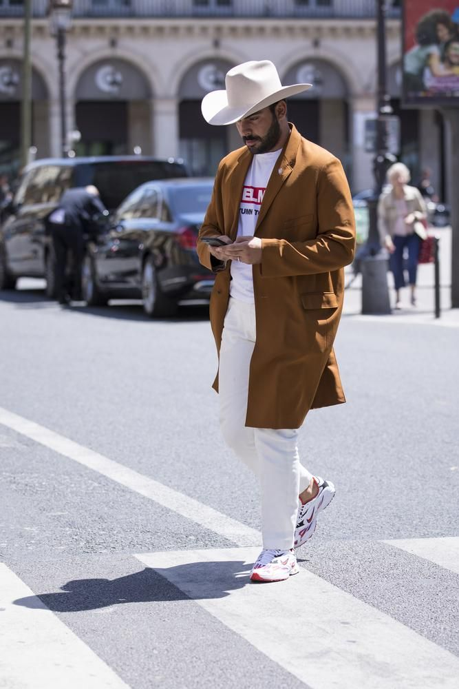 A guest at Paris Fashion Week struts into a show wearing a honking cowboy hat.