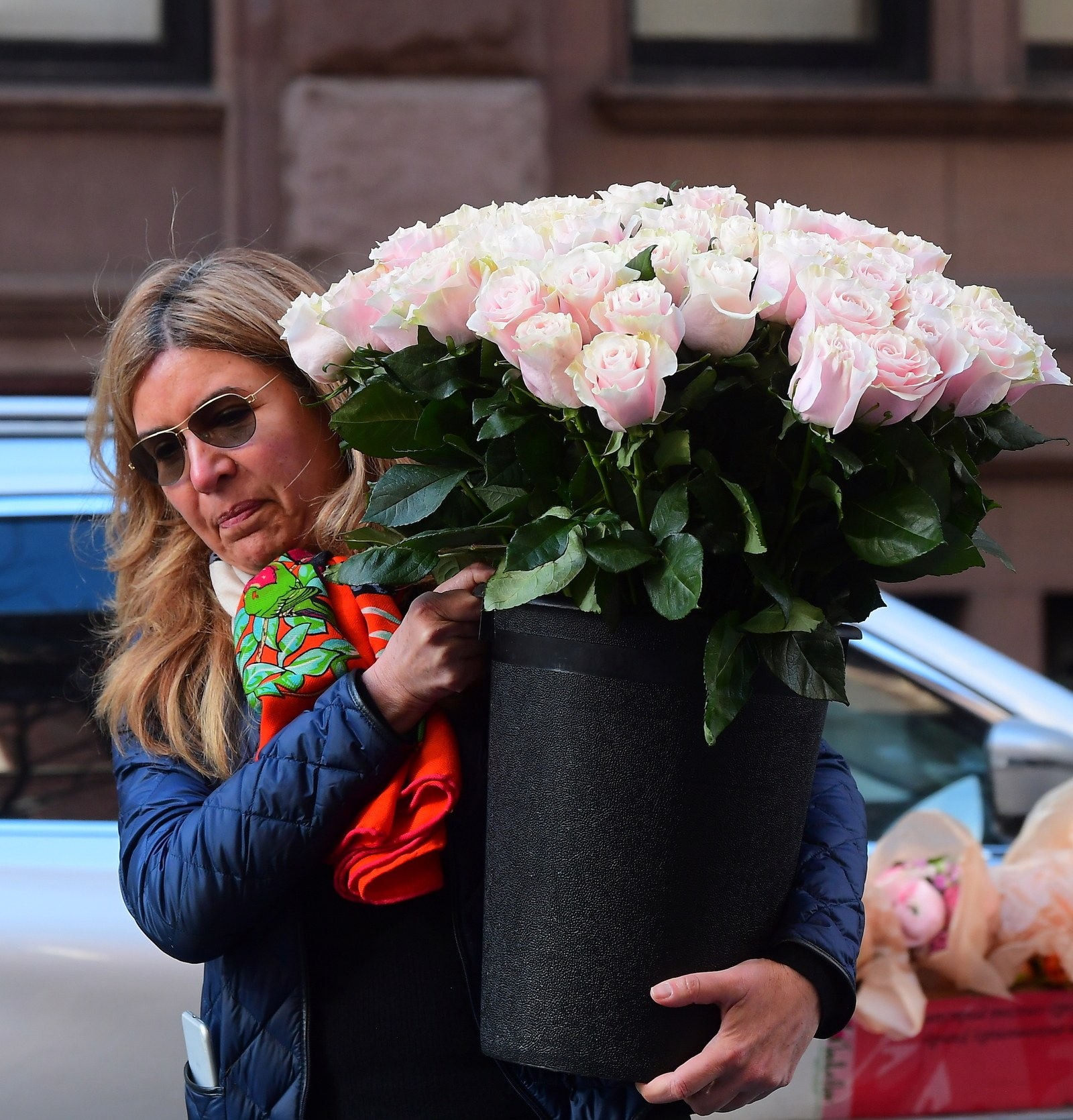 A woman carrying a bouquet of flowers into what is reportedly Meghan Markle's baby shower.