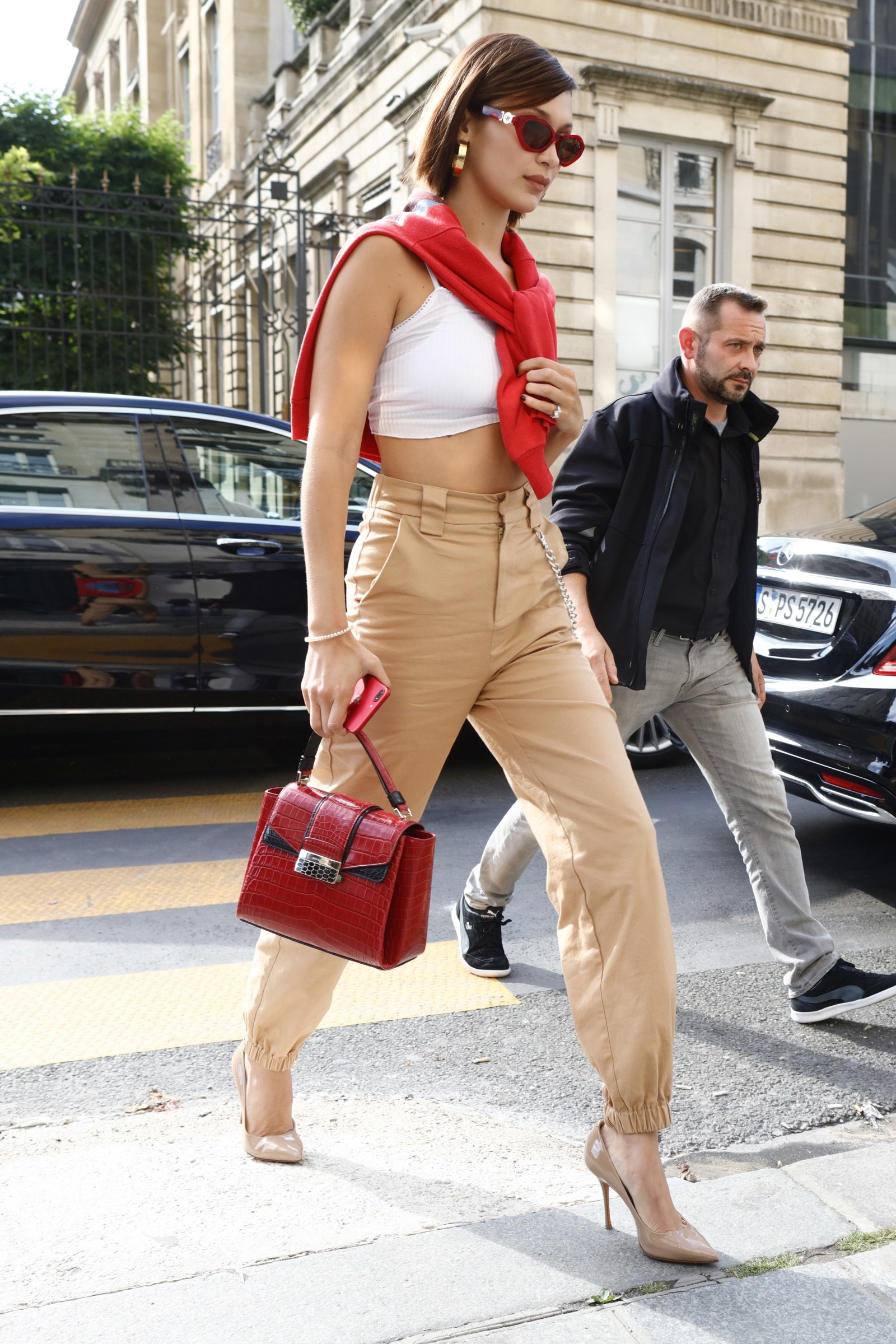 woman wearing cropped white cami with beige cargo pants and heels