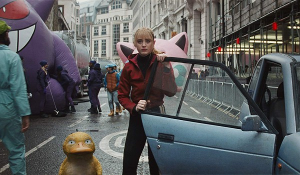 Detective Pikachu Lucy and Psyduck stand in the street during parade prep