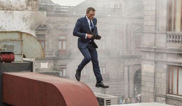 Daniel Craig as James Bond runs on a rooftop in the opening scene to Spectre