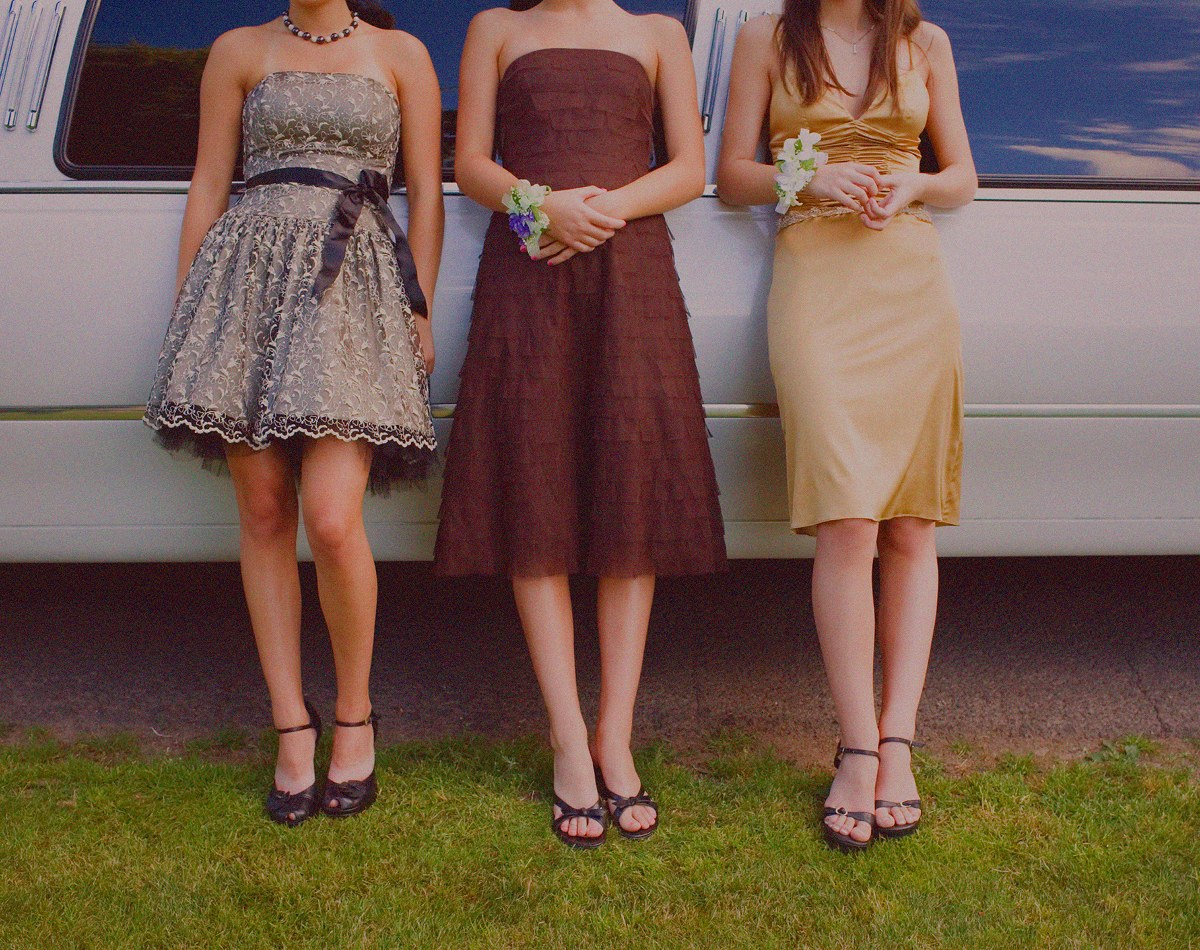 three girls in prom dresses leaning against a car