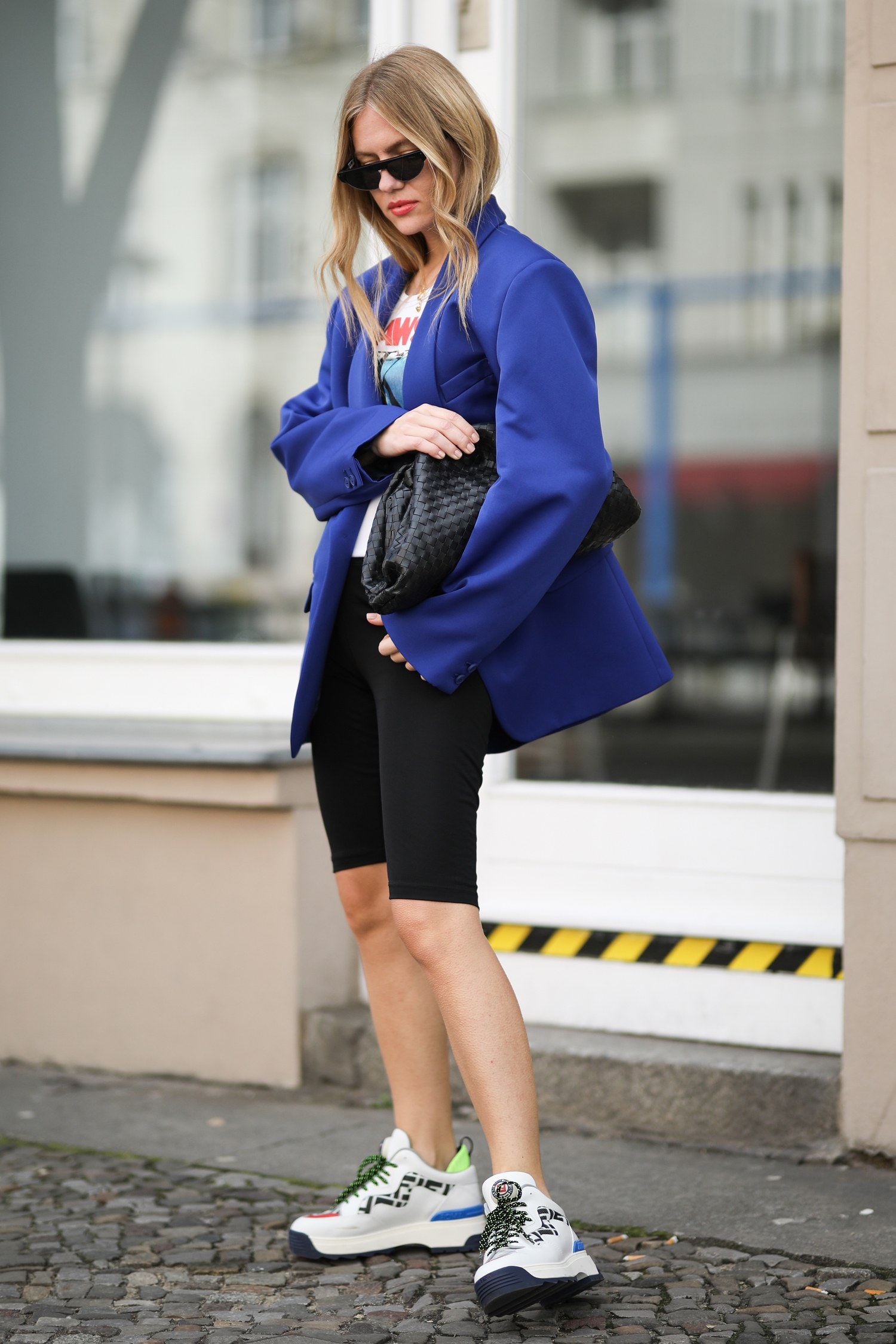 woman wearing a white graphic tshirt under a purple blazer and black bike shorts with sneakers