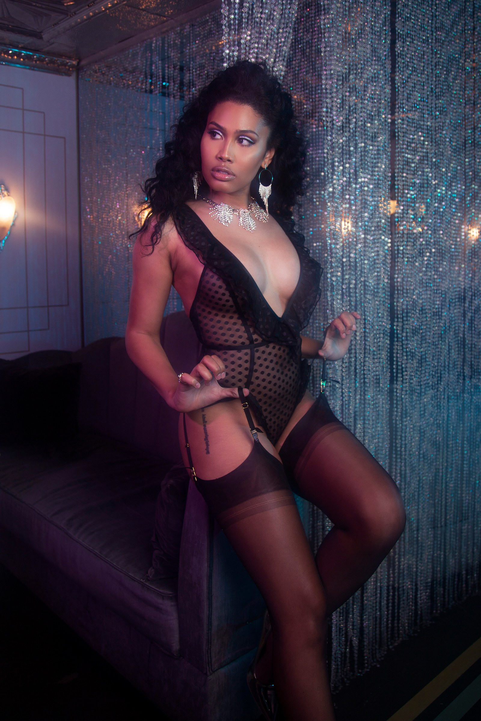 woman posing in a black sheer bodysuit and stockings