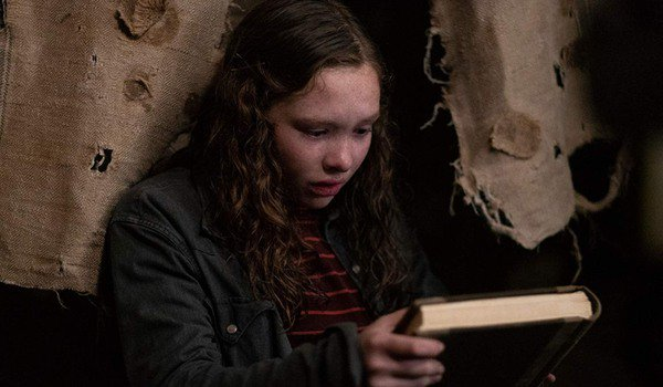 Scary Stories To Tell In The Dark Stella holds the book while hiding in the Bellows house