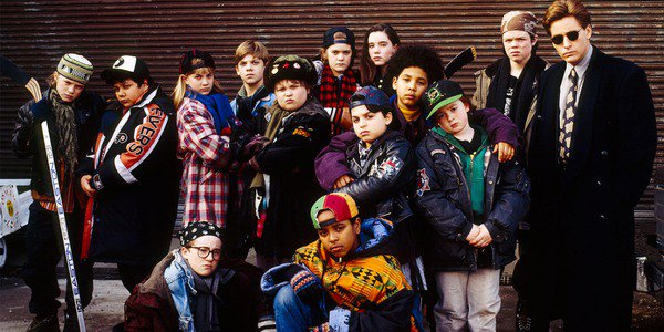 The Mighty Ducks team and coach lineup in front of a brick wall