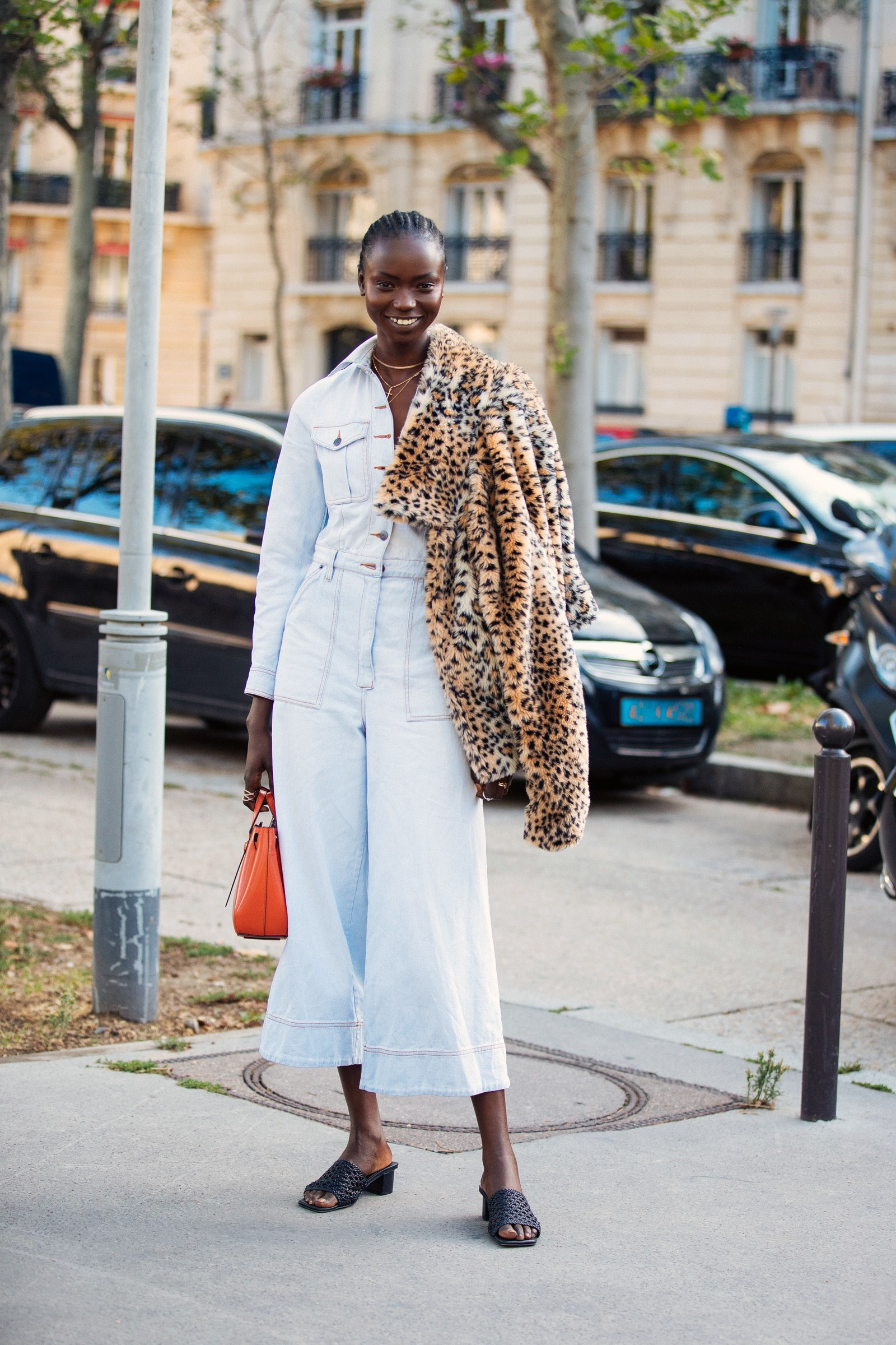PARIS FRANCE SEPTEMBER 27 Model Agi Akur wears a white jumpsuit orange Loewe bag black sandals and carries a leopard...