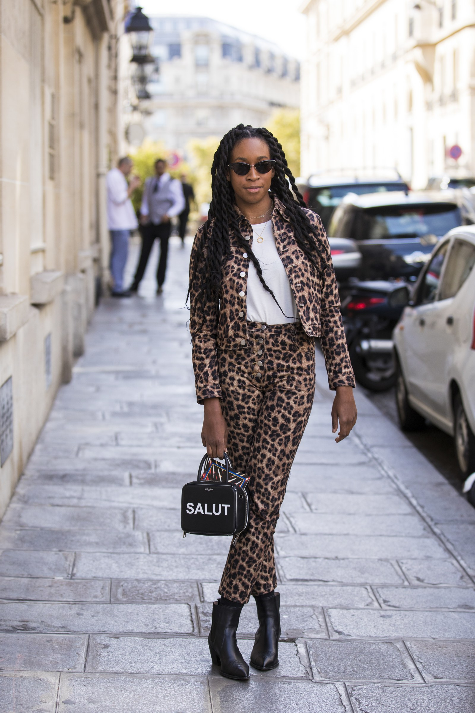 A guest wearing a white tshirt leopard print jacket with matching pants black boots and black printed bag is seen before...