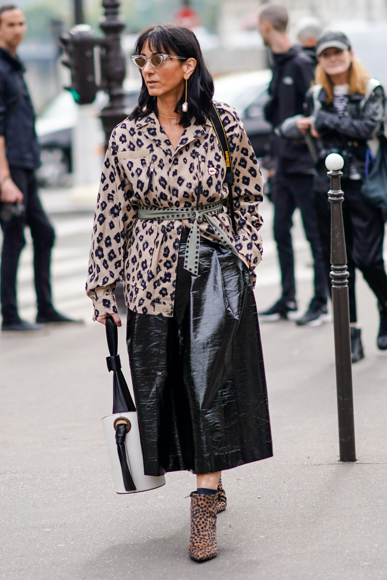 A guest wears sunglasses a beige leopard print coat a grey eyelet belt a black and white bag leopard print ankle boots...